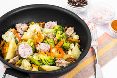 Vegetable stew with sausage grilled slices in a frying pan on a Royalty Free Stock Photo
