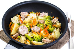 Vegetable stew with sausage grilled slices in a frying pan on a Stock Photos