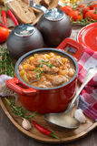 Vegetable stew with sausages in a pan, vertical Stock Photo