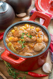 Vegetable stew with sausages in a red pan, vertical Royalty Free Stock Image
