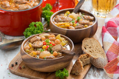 Vegetable stew with sausages in a wooden bowl on board and bread Royalty Free Stock Images