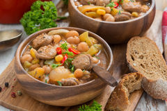 Vegetable stew with sausages in a wooden bowl on board and bread Stock Image