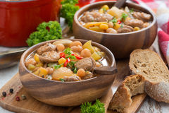 Vegetable stew with sausages in a wooden bowl, close-up Royalty Free Stock Photo