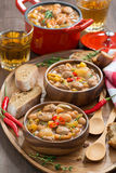 Vegetable stew with sausages in wooden bowl, vertical, top view Royalty Free Stock Photos