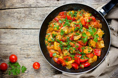 Vegetable stir-fry in frying pan. Vegetarian saute with eggplant, paprika, tomato, garlic and parsley stock image