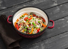 Vegetable stir fry and rice noodles in an enamel bowl on a dark wooden background. Royalty Free Stock Image