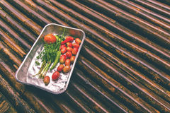 Vegetable in tray on the bamboo floor after raining. Used color tool for vintage tone Royalty Free Stock Photo