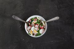 Vegetable vegan salad of ramson, radish, green onions and boiled. Eggs in a white plate on a dark concrete background, in retro treatment. Close-up, top view Stock Photo