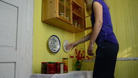 Vegetable winter use. Housewife prioritizes jars the wooden cupboard shelves with canned vegetables for winter use stock video footage