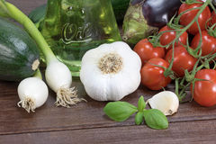 Vegetable on the wooden table. General view of the zucchini; eggplant, garlic, onion, basil leaves  and cherry tomatoes lying on a wooden table. Bottle with Stock Photography