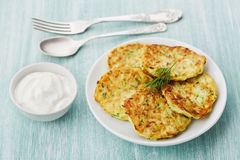 Vegetable zucchini cabbage pancakes or fritters with sour cream on wooden table Stock Image