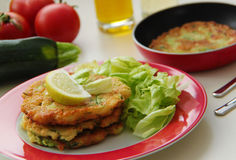 Vegetable zucchini pancakes served with fresh salad. Ingredients for cooking on background. Close up view. Stock Image