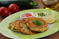 Vegetable zucchini pancakes served with yogurt and tomato sauce. Ingredients for cooking on background. Close up view. Stock Photos