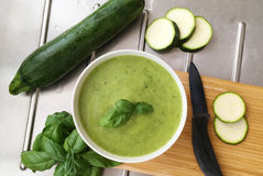 Vegetable zucchini soup and ingredients for cooking. Whole zucchini, slices of zucchini and basil herbs on stainless steel table. Zucchini soup puree and Stock Images