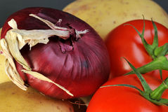 Vegetables. Fresh onion tomatoes and potatoes Stock Photography