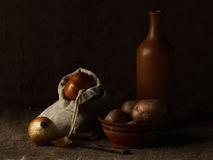 Vegetables. Little sack with bulbs, dish with a potato, ceramics Stock Photo