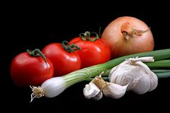 Vegetables. Tomatoes, onion, spring onion and garlic, isolated on a black background stock photography