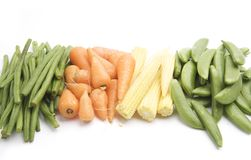 Vegetables. Fresh Baby Carrots, Baby Corn, Long Green Beans and Sugar Snaps, isolated on a white background table, lit with a large light source from the above royalty free stock photo