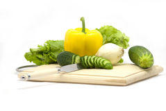 Vegetables. Cucumber and yellow pepper lie on a chopping board Royalty Free Stock Image
