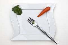 The vegetables. A carrot and a pea on a fork with a white plate, decorated with parsley Stock Images