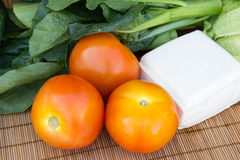 Vegetables. Fresh vegetables, tomatoes and tofu on bamboo mat Royalty Free Stock Photos