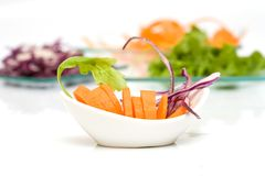Vegetables. Some vegetables on a white bowl with salad on platter stock image