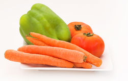 Vegetables. Tomato, paprika and carrots on a plate Stock Photography