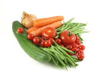 Vegetables. Variety of raw vegetables: cucumber, tomatoes, green beans, cherry tomatoes, onion, carrots royalty free stock images