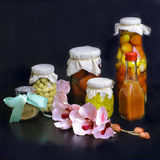 Vegetables allsorts. A composition from jars with vegetables and a magnolia branch Stock Images