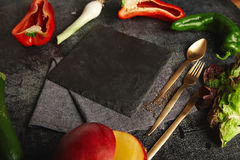 Vegetables around a black slate cheese board Stock Photo