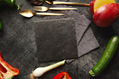 Vegetables around a black slate cheese board. Peppers, leeks, zucchini and mango with golden utensils lying around an empty black slate board on black background stock photos