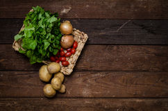 Vegetables background. Potatoes with tomatoes on wooden floor Royalty Free Stock Photo
