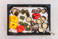 Vegetables on a baking tray. Baked pieces of red and yellow peppers, zucchini, and eggplants royalty free stock image