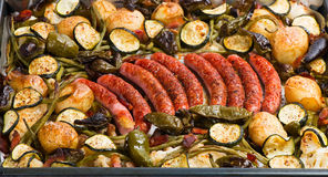 Vegetables and banger. Baked in a oven potatoes with vegetables and sausages on a oven-tray Royalty Free Stock Photo