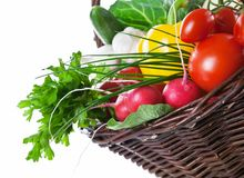Vegetables Basket. Composition with raw vegetables, green leaves and wicker basket isolated on white background. Copy space Royalty Free Stock Images