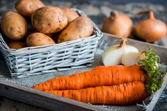 Vegetables in a basket: beets, onions, garlic, dill, potatoes, carrots on an old wooden background. Vegetables in a basket: beets, onions, garlic, dill, potatoes Royalty Free Stock Photos
