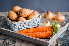 Vegetables in a basket: beets, onions, garlic, dill, potatoes, carrots on an old wooden background. Vegetables in a basket: beets, onions, garlic, dill, potatoes Royalty Free Stock Image