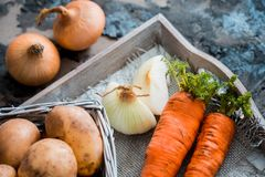 Vegetables in a basket: beets, onions, garlic, dill, potatoes, carrots on an old wooden background. Vegetables in a basket: beets, onions, garlic, dill, potatoes Stock Photo