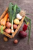 Vegetables in a basket: beets, onions, garlic, dill, potatoes, carrots. On an old wooden background Royalty Free Stock Images