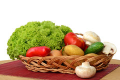 Vegetables in a basket. Fresh vegetables in a basket over a red bamboo, on wooden table Stock Photos