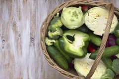 Vegetables in the basket on white painted wooden background: cucumber, broccoli, pepper, cabbage, kohlrabi. Royalty Free Stock Photography