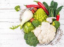 Vegetables in basket on white rustic wood. Royalty Free Stock Images