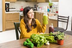Vegetables Are Beneficial For Health. Fit Latin woman looking at vegetable smoothie while following green diet stock photo