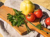 Vegetables on a blackboard, tomato and green onions on a wooden Royalty Free Stock Photography
