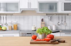Vegetables and blurred view of kitchen interior on background royalty free stock photos