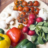 Vegetables on board. Some vegetables arranged on wooden chopping board. Tomatoes, garlic, mushrooms, peppers, radishes stock photo