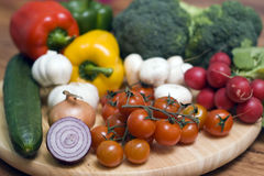 Vegetables on board. Some vegetables arranged on a round wooden chopping board. Tomatoes, mushrooms, peppers, broccoli Stock Image
