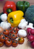 Vegetables on board. Some vegetables arranged on wooden chopping board. Tomatoes, garlic, mushrooms, peppers, broccoli Stock Image
