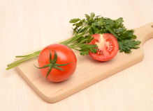 Vegetables on a board. Tomatoes and parsley on a board on a table in bright kitchen Stock Image