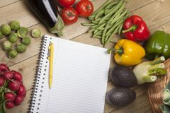 Vegetables with book and pen on wooden surface. High angle view of vegetables with book and pen on wooden surface Royalty Free Stock Photo